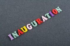 Iinauguration Engelska uttrycker på svart brädebakgrund som komponeras från träbokstäver för färgrikt abc-alfabetkvarter, kopia Arkivfoto