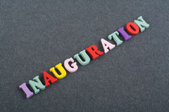 Iinauguration . English word on black board background composed from colorful abc alphabet block wooden letters, copy. Space for ad text. Learning english stock photo