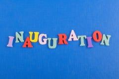 Iinauguration Palabra inglesa en el fondo azul compuesto de letras de madera del ABC del bloque colorido del alfabeto, espacio de Fotos de archivo