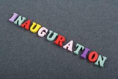 Iinauguration Palabra inglesa en el fondo negro compuesto de letras de madera del ABC del bloque colorido del alfabeto, copia del Imágenes de archivo libres de regalías