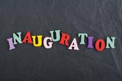Iinauguration Palabra inglesa en el fondo negro compuesto de letras de madera del ABC del bloque colorido del alfabeto, copia del Fotografía de archivo libre de regalías