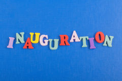 Iinauguration Parola inglese su fondo blu composto dalle lettere di legno di ABC del blocchetto variopinto di alfabeto, spazio de Fotografie Stock
