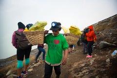 IJEN INDONESIEN - 11 11 2017: Svavelgruvarbetare som bär svavel-laden korgar på den Kawah Ijen vulkan i Java, Indonesien Arkivbilder
