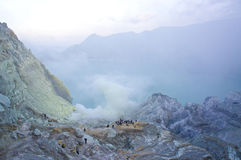 Ijen volcano in East Java contains the world's largest acidic volcanic crater lake, called Kawah Ijen. Spewing out sulphur smoke in the morning. Sun is hidden Stock Photo