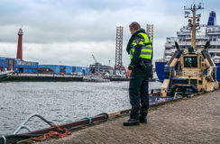 Ijmuiden, Netherlands - August 16 2015 : Police man checking the borders of the harbour Royalty Free Stock Image