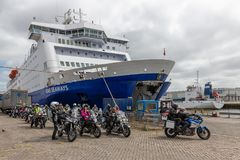 Ferry in Dutch harbor IJmuiden with motorcyclists embarking the ship. IJmuiden, The Netherlands - May 17, 2018: Ferry in Dutch harbor IJmuiden preparing to leave royalty free stock image