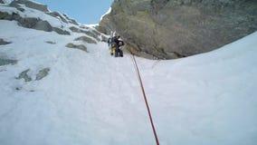 Ijs die beklimmen: bergbeklimmer op een gemengde route van sneeuw en rotsduri stock footage