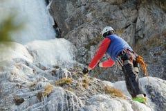 Ijs die bergbeklimmer op de winter natuurlijke rotsen beklimmen openlucht stock foto