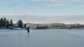 Ijs die op een bevroren meer schaatsen stock video