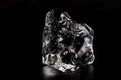 Ijs op een zwarte lijst Het smelten stuk van bevroren water in een warme ro Stock Afbeeldingen