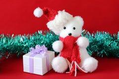 Ijsbeer die een hoed en een rode die sjaal dragen naast giften met glanzende knopen op een decor van de Kerstmisvakantie wordt ge Stock Fotografie