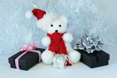 Ijsbeer die een hoed en een rode die sjaal dragen naast giften met glanzende knopen op een decor van de Kerstmisvakantie wordt ge Stock Afbeeldingen