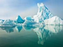 Ijsbergen die in Kalm Water drijven Stock Afbeeldingen
