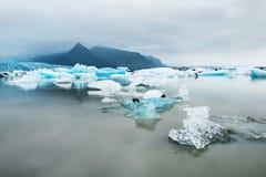 Ijsbergen in het ijzige meer met bergmeningen Stock Foto