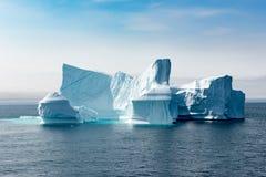 Ijsbergen met turkoois glanzend water, Groenland De ijsbergbouw met toren royalty-vrije stock afbeeldingen