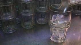 Ijsblokje die in een glas vallen De kelner bereidt verse drank in een restaurant voor stock videobeelden