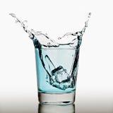 Ijsblokjes die in glas water bespatten Stock Afbeeldingen