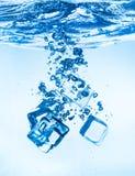 Ijsblokjes die onder water vallen royalty-vrije stock fotografie