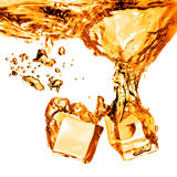 Ijsblokjes die in oranje water met plons worden gelaten vallen die op whit wordt geïsoleerd Stock Foto