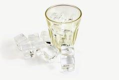 Ijsblokjes en glas op wit worden geïsoleerd dat Royalty-vrije Stock Afbeelding