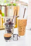 Ijsblokjes van zwarte koffie met kleine kop van hete espresso worden gemaakt die Stock Afbeeldingen