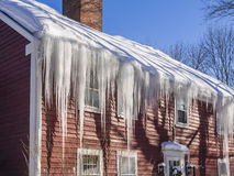Ijsdammen en sneeuw op dak en goten Stock Foto's