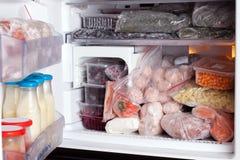 Ijskast met bevroren voedselvlees, melk, vruchten en groenten royalty-vrije stock fotografie