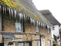 Ijskegels die van een met stro bedekt dak hangen. Stock Afbeeldingen