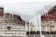 Ijskegels en sneeuw het hangen van de bouw van dak Stock Afbeelding