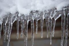 Ijskegels en sneeuw op dakclose-up Het concept van het de winterweer Bevroor en ijsachtergrond Sneeuw en ijskegel Bevroren over w stock foto