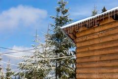 Ijskegels en sneeuw op een oud houten plattelandshuisje Stock Afbeelding