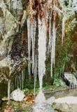Ijskegels onder een waterval stock foto's
