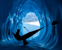 Ijsklimmer die in hangmat binnen een diep blauw ijshol rust in de Matanuska-Gletsjer van Alaska stock foto