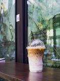 Ijskoffie latte in meeneemkop op houten lijst Meeneemijs latte in plastic kop met stro op houten lijst De achtergrond w van de ko stock foto