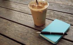 Ijskoffie in meeneemkop met notitieboekje en pen aan de kant BO stock foto