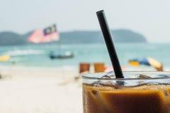 Ijskoffie met een Maleise vlag op de achtergrond Het genieten van vakantie van concept stock foto