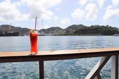 Ijskoude drank op een spoor met oceaan en tropische eilandscènes op de achtergrond stock foto's