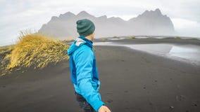 IJsland - Jonge mens die een selfie met bergen op een zwart zandstrand nemen royalty-vrije stock afbeelding