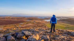IJsland - Mens die zich bij de heuvel bevinden die enorme weide en fjordmening overzien royalty-vrije stock foto