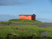 IJsland, op de weg, blauwe hemel, noodsituatiechalet, bergen, rotsen Stock Foto