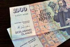 Ijslands contant geld Geld van IJsland 1000 Ijslandse kroonrekeningen op houten lijst De Ijslandse kroon is de nationale valuta v stock foto's