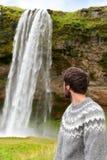 Ijslandse sweatermens door waterval op IJsland Stock Afbeelding