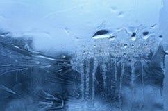 Ijspatroon en bevroren waterdalingen op het glas van het de wintervenster stock foto