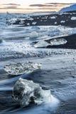 Ijsstukken bij een zwart strand stock foto's
