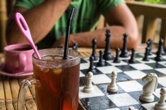 Ijsthee en koffie terwijl het spelen van schaak stock afbeelding