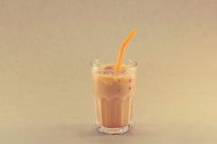 Ijsthee met melk in glaskop op korreldocument achtergrond Stock Foto