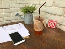 Ijsthee in plastic glazen, glazen, smartphones en documenten op de houten lijst naast de witte muur met het concept relaxin Royalty-vrije Stock Foto's