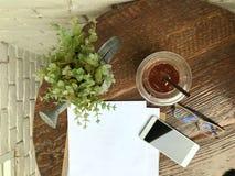 Ijsthee in plastic glazen, glazen, smartphones en documenten op de houten lijst naast de witte muur met het concept relaxin Stock Afbeeldingen