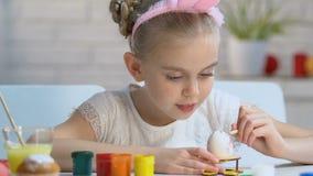 Ijverig meisje die zorgvuldig patroon met verven op ei, Pasen-decoratie zetten stock videobeelden