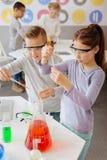 Ijverige klasgenoten die chemische producten toevoegen aan steekproefbuizen stock afbeelding